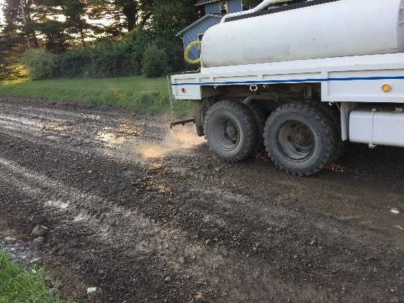 Apply the ROAD-HARD additive with a water truck.